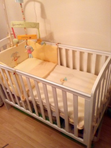 Amelia's cot with the Pumpkin & Popsicle bedding set; bumper, lemon fitted sheet, fleece blanket and mobile.